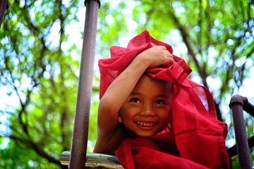 Boy Holding Red Textile Covering His Head