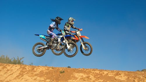 Two Person Riding Motocross Dirt Bikes