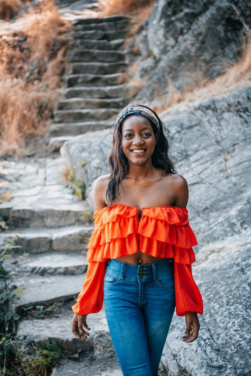 Woman in Orange Off Shoulder Top Standing on Concrete Stairs