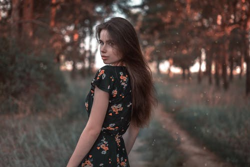 Woman in Black and Red Floral Dress Standing Near Trees