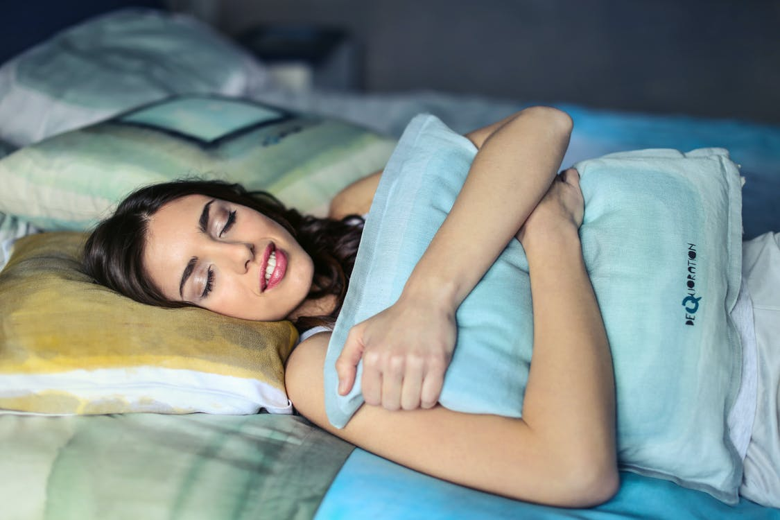 Photo of a Woman Hugging a Blue Pillow