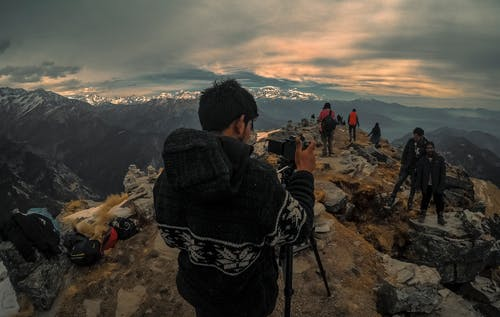Man Taking Photo of Couple on Mountain Range