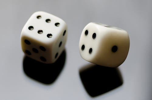 Two White-and-black Dice on Black Surface