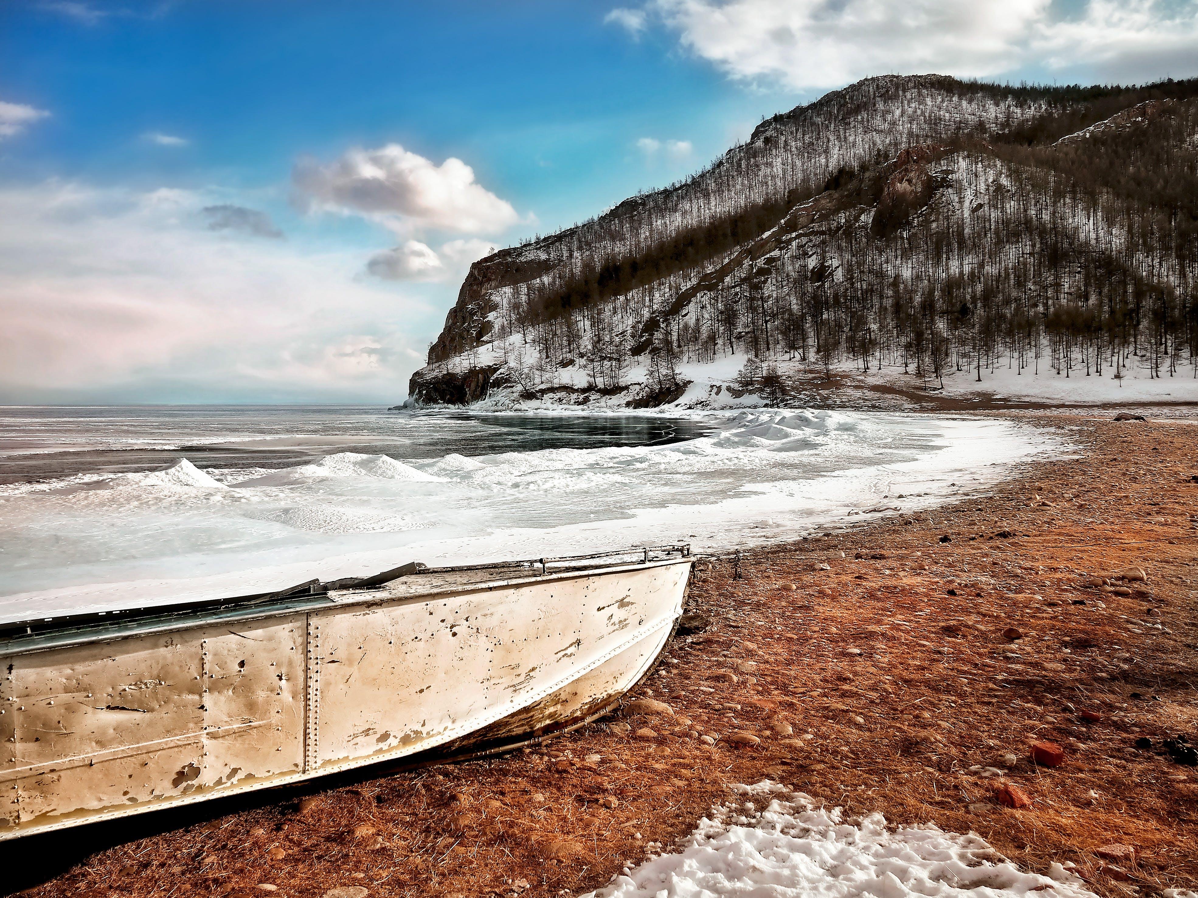 White Boat on Seashore Near Mountain Under White and Blue Sky