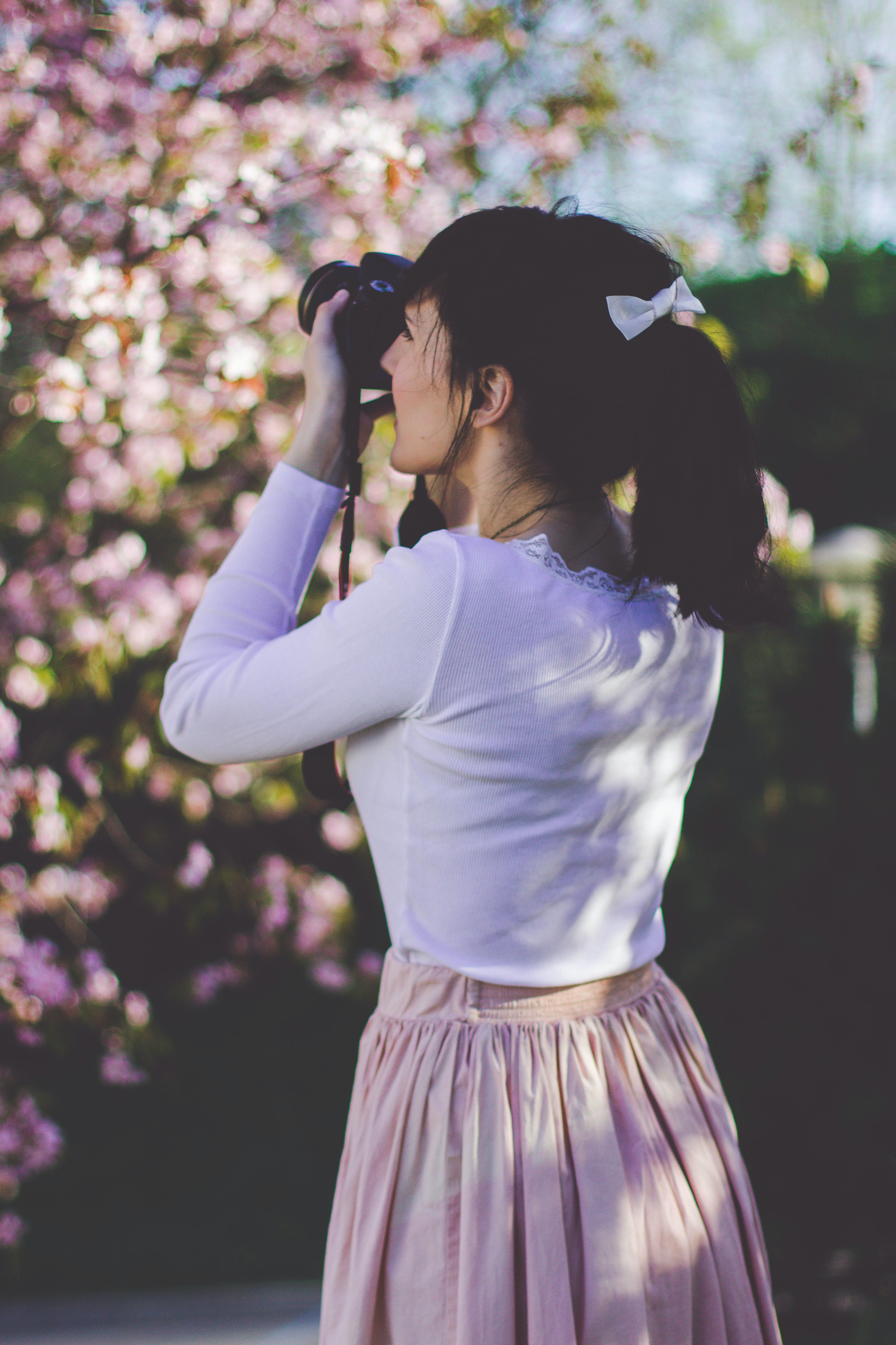 Woman in Pink Skirt Holding Camera Try to Picture the Tree