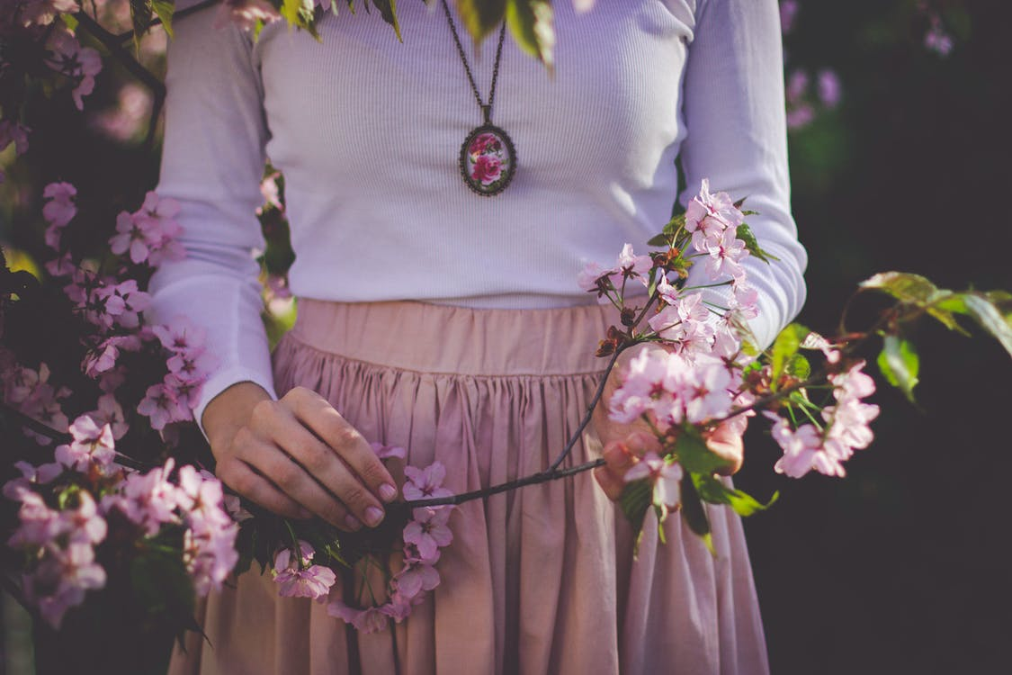 Woman Wearing White Long Sleeve Shirt and Beige Skirt Holding Pink Petaled Flower