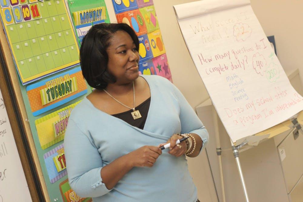 A pleasant woman teaching at school.   Photo: Pexels