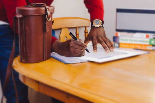 Person Holding a Pen and Paper