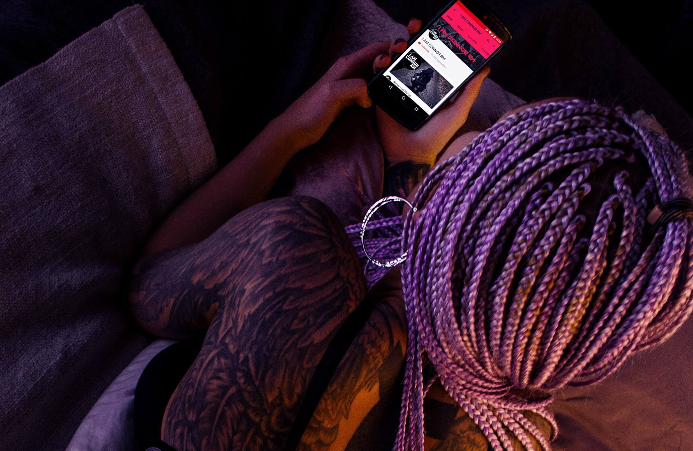 Woman with Purple Braided Hair Holding an Android Smartphone