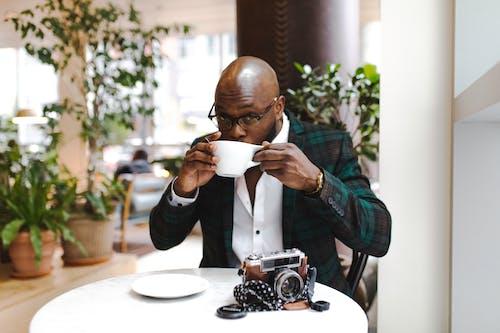 흰색 세라믹 머그잔에서 홀짝이는 동안 원탁 앞에 앉아있는 남자