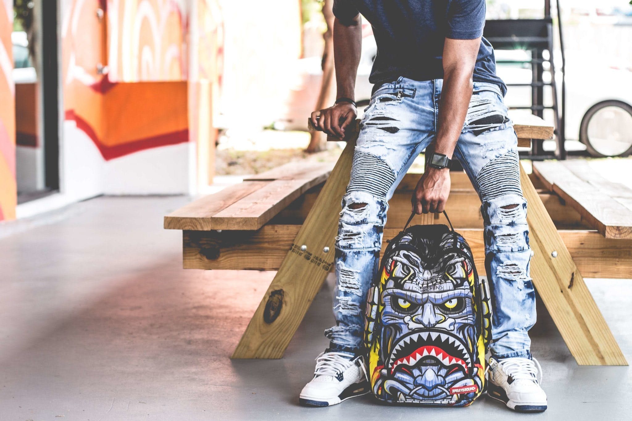 Man Wearing Distressed Denim Pants Holding Multicolored Backpack