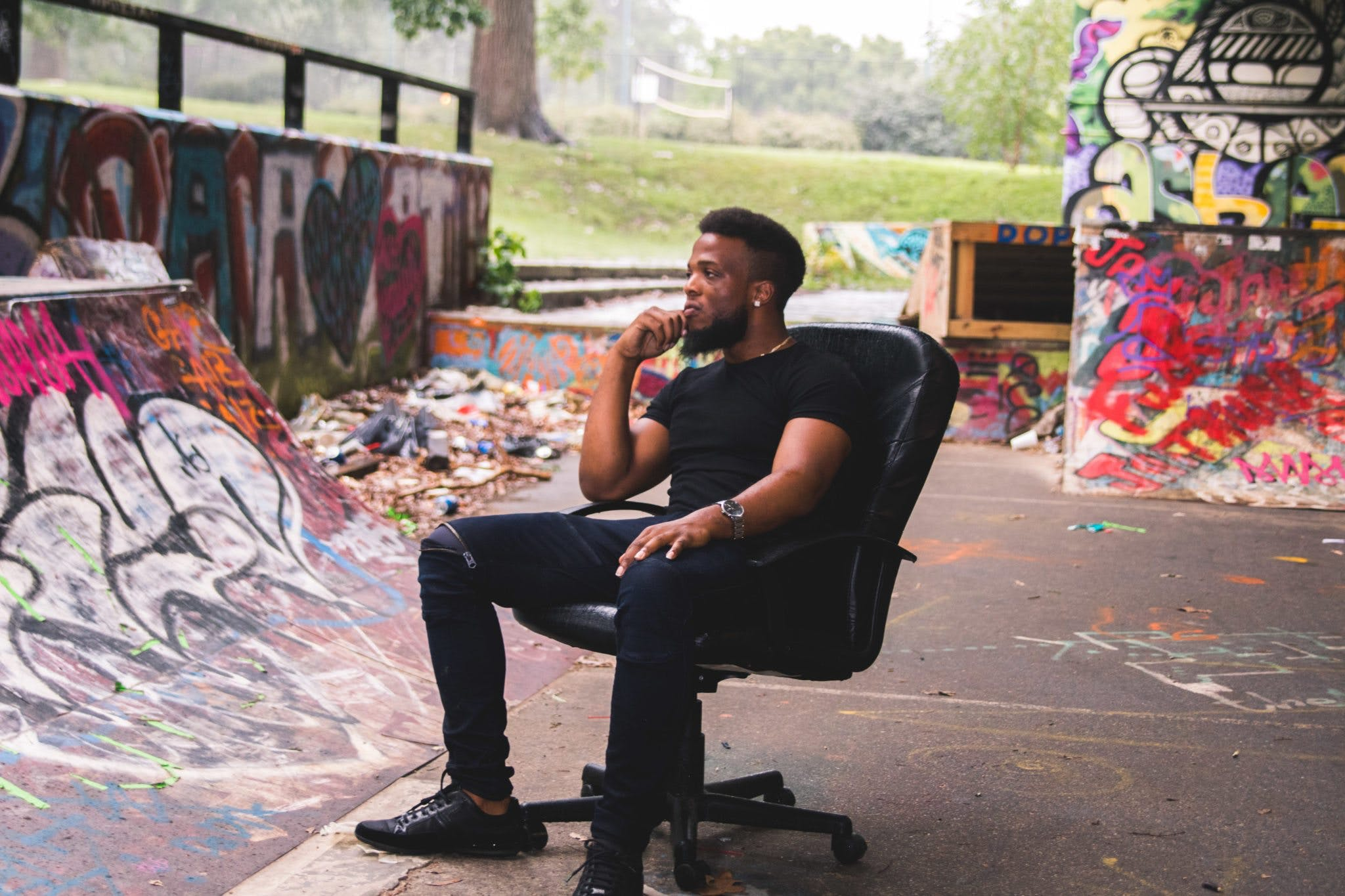 Man Wearing Black Crew-neck Shirt Sitting on Leather Rolling Chair