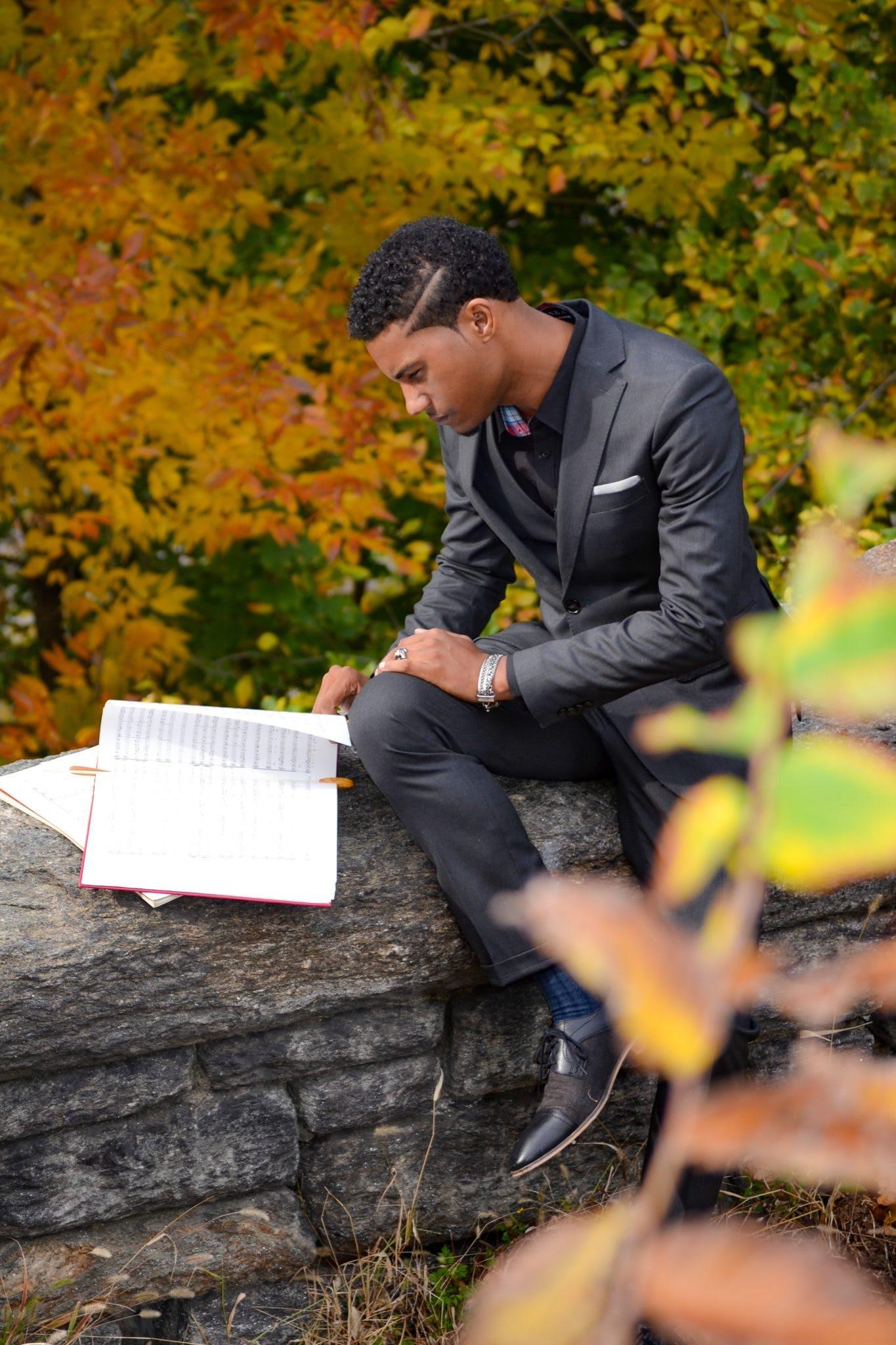Man Wearing Black Suit Reading Book
