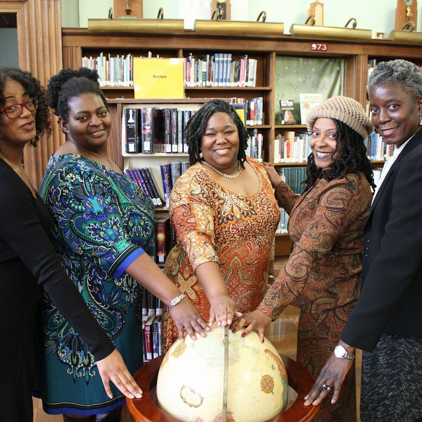 Five Women with Hands on top of a Wooden Globe