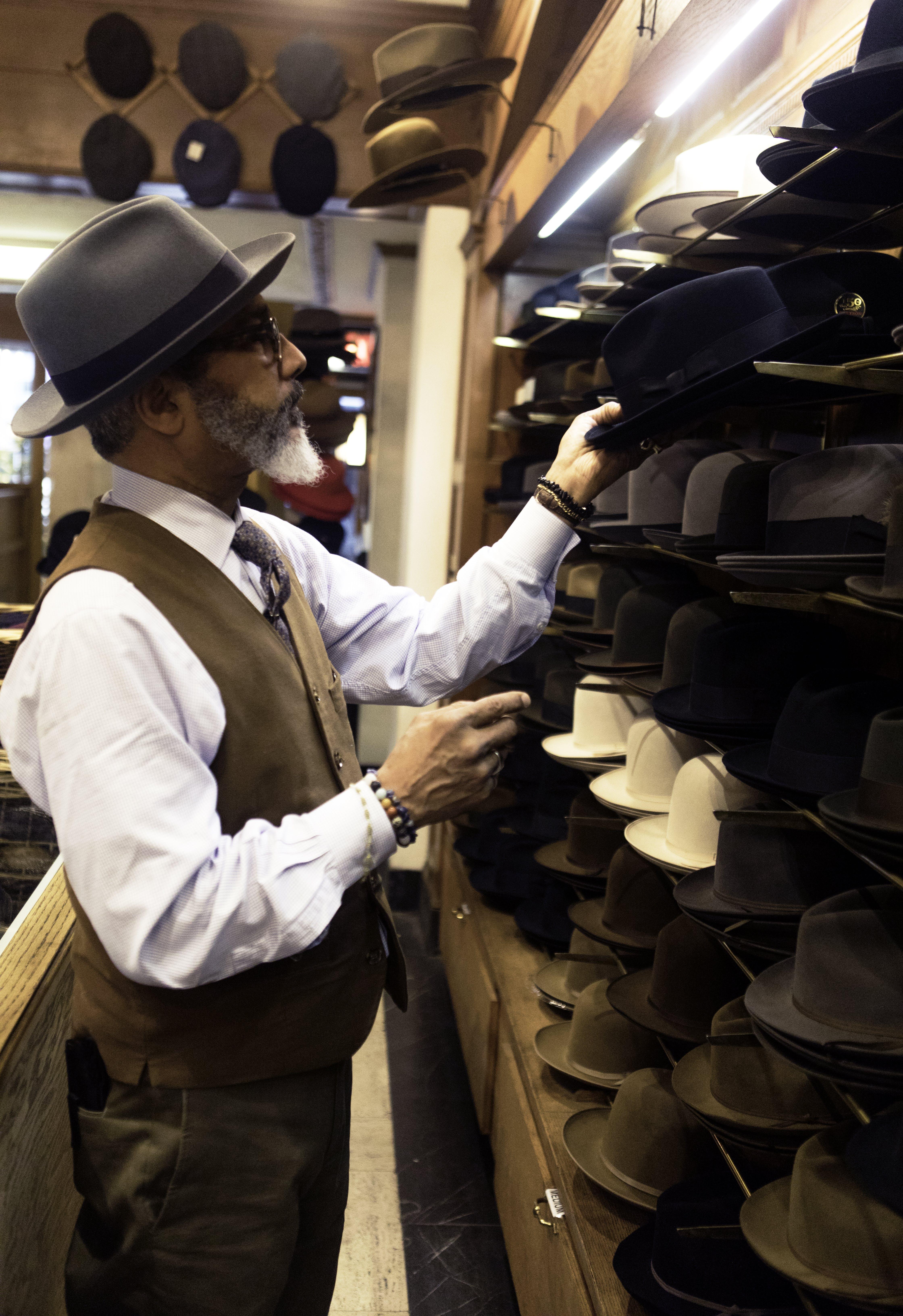 Man Picking Hats in Rack