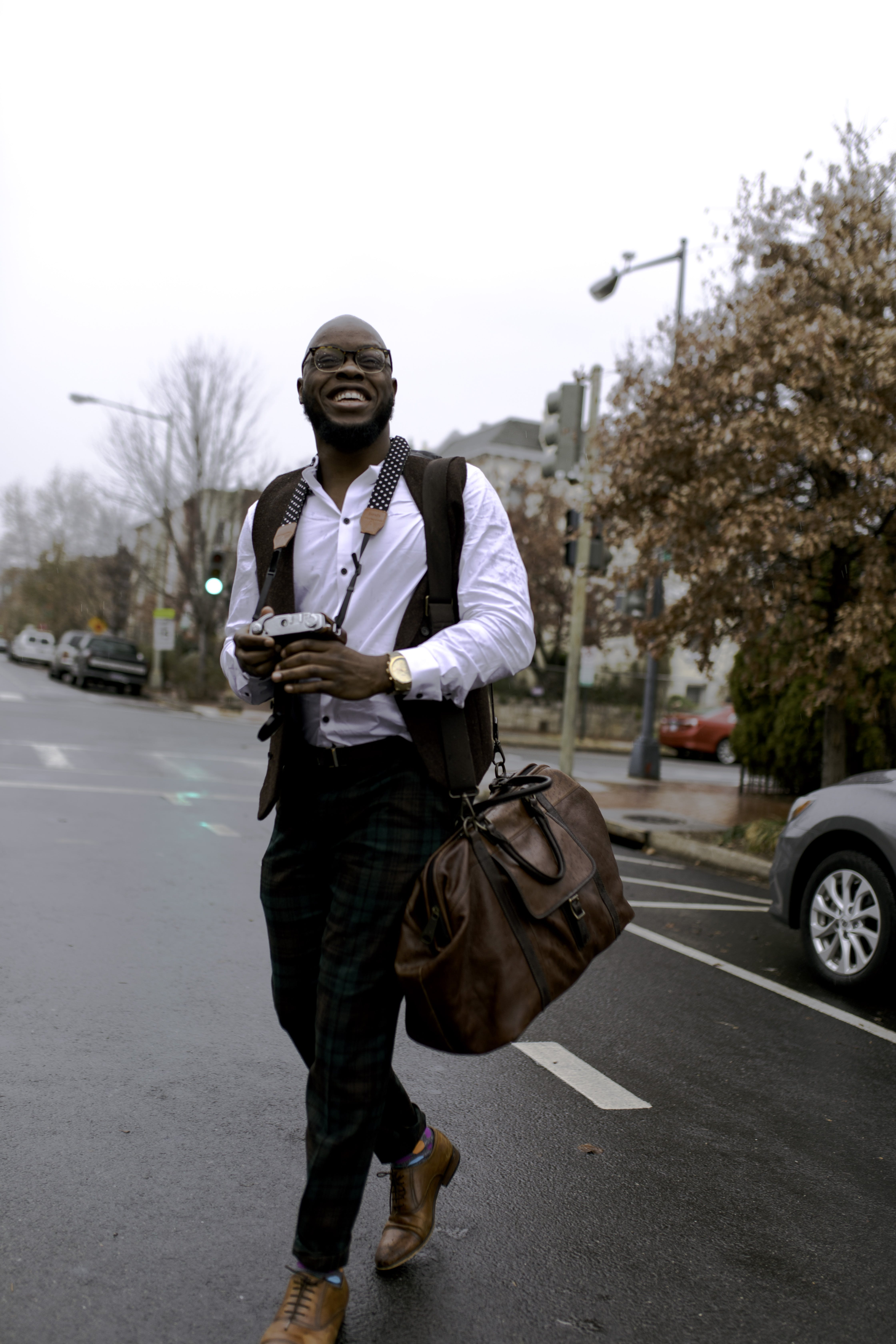 Man in White Button-up Dress Shirt Holding Camera While Smiling and Crossing Street