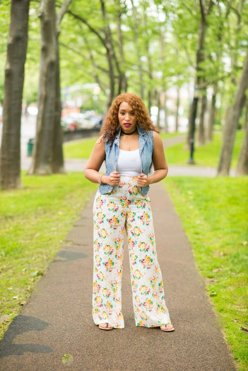 Woman in White Shirt with Denim Vest and Floral Pants