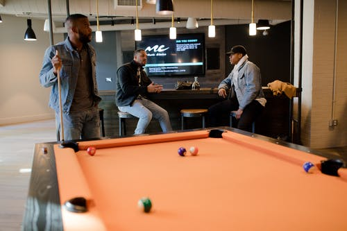 Man in Blue Denim Jacket Holding Cue Stick