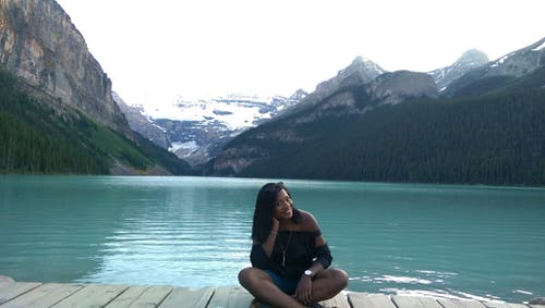 Woman With Black Off-shoulder Top Sitting on Wooden Dock Beside Blue Ocean With Mountain in Background