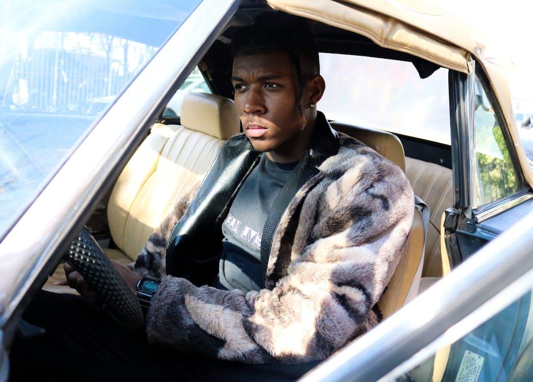 Man Sits on Car