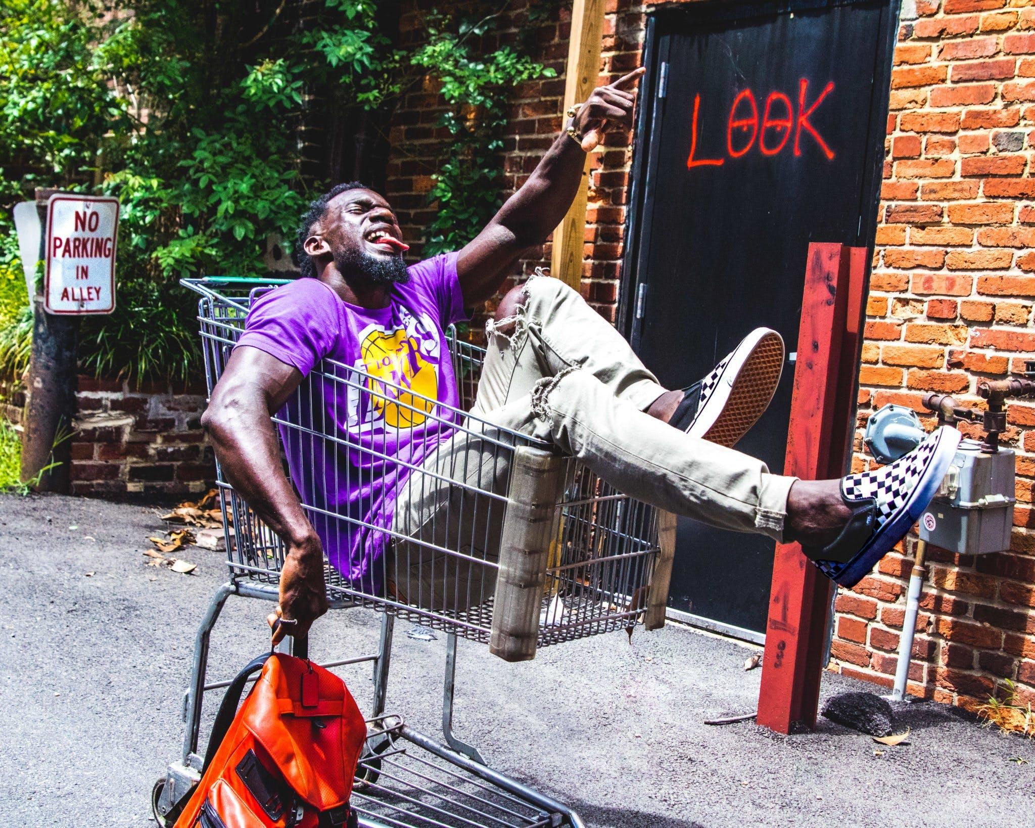 Man Sitting on Shopping Cart