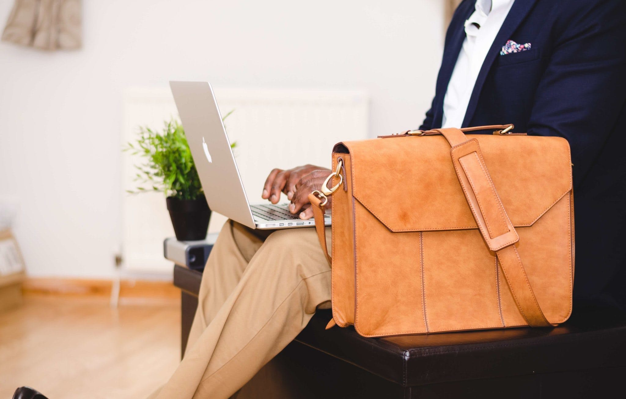 Person Wearing Blue Suit Beside Crossbody Bag and Using Macbook