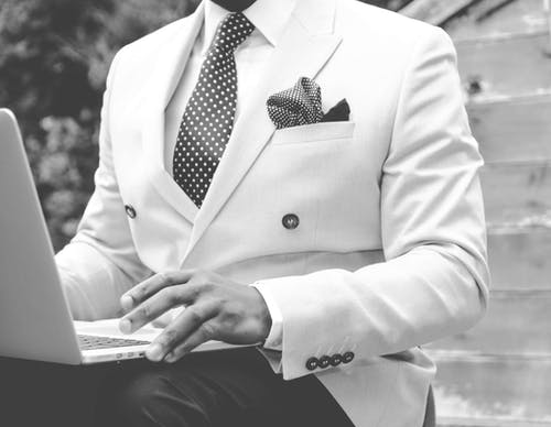 Grayscale Photo of Man Wearing White Suit Jacket