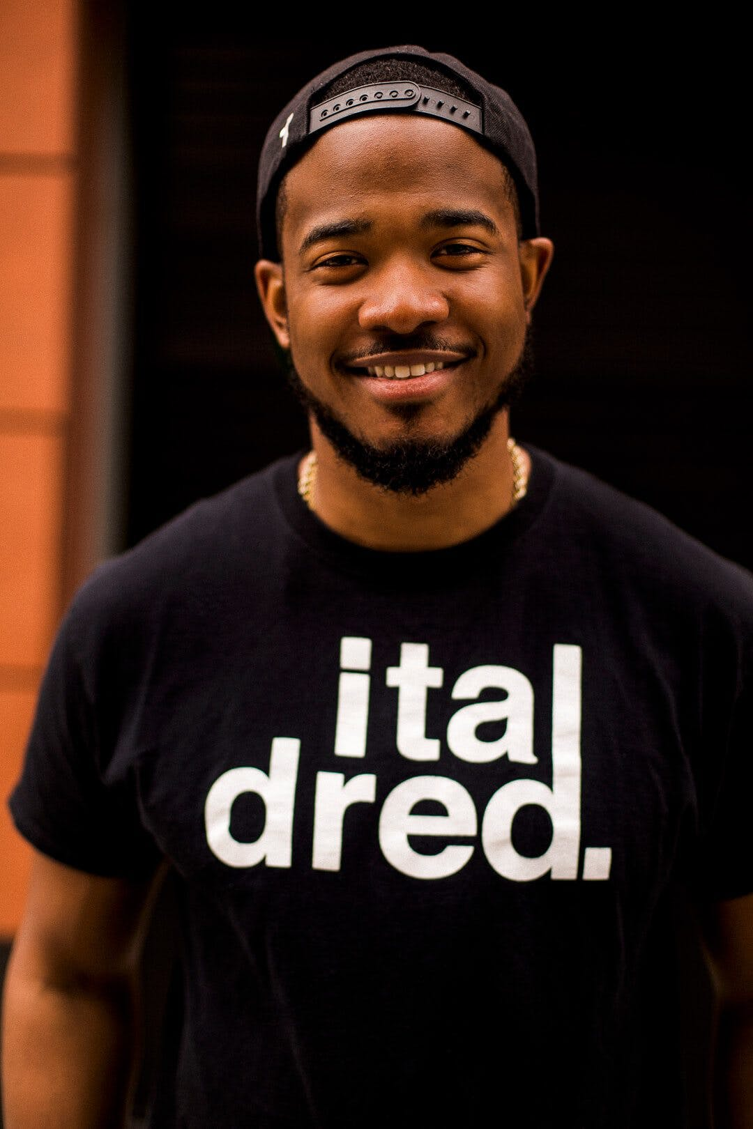 Smiling Man Wearing Black Snapback Cap and Black Crew-neck Shirt