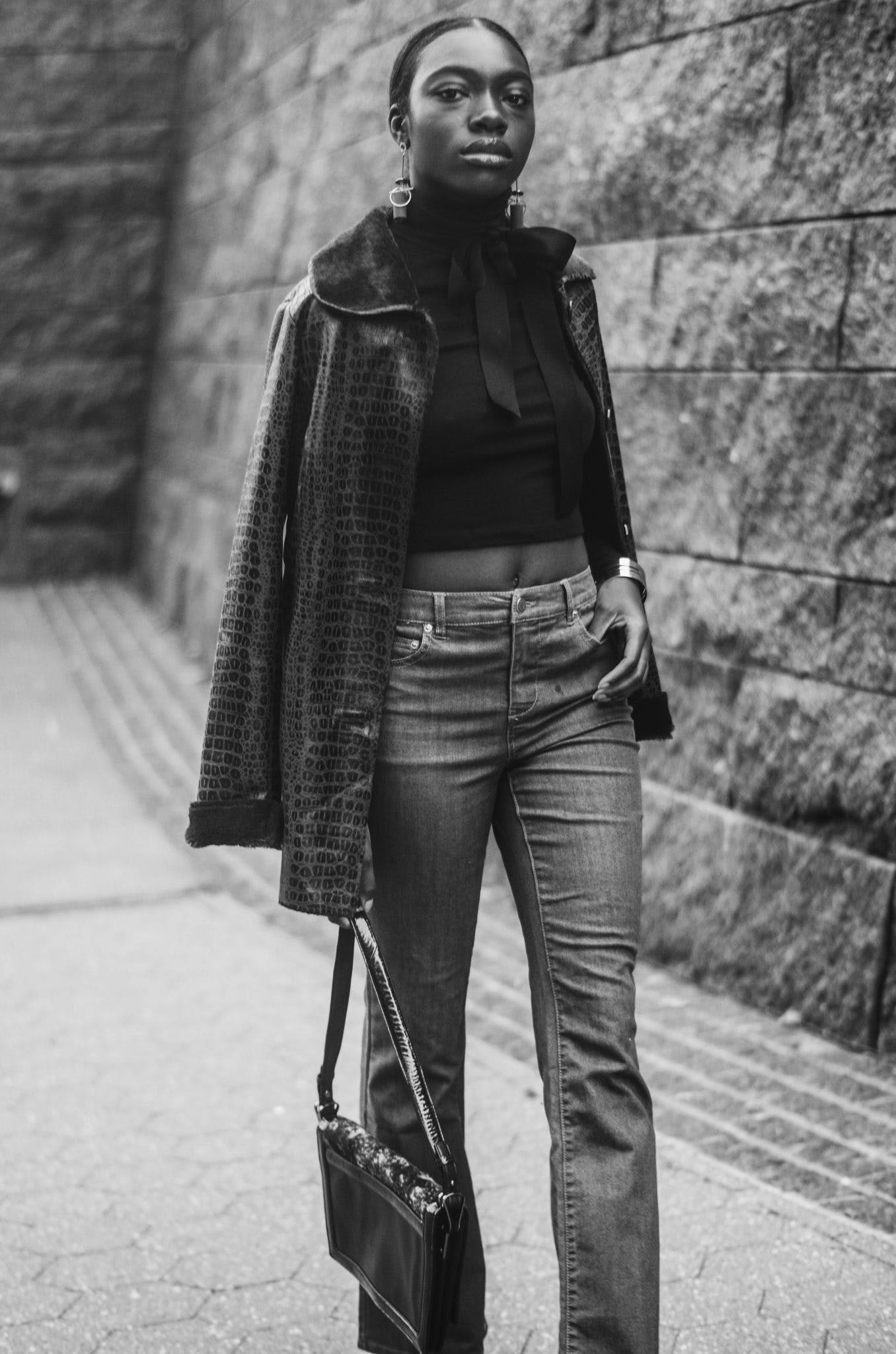 Woman in Jacket, Crop Top, and Pants Holding Bag