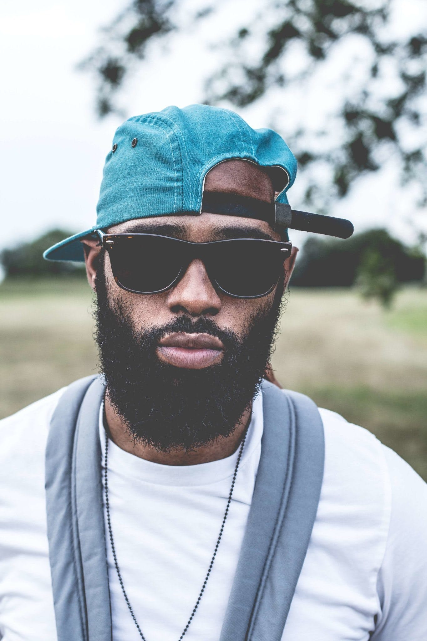 Man Wearing Sunglasses and Denim Strap Back Cap