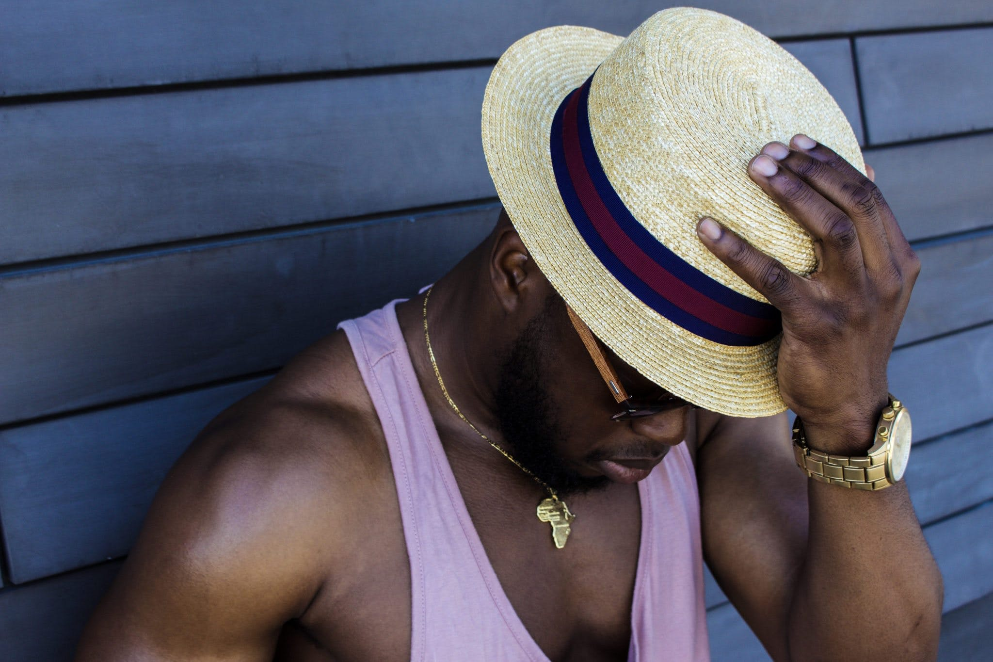 Man Wearing Purple Tank Top, Gold-colored Necklace, Gold-colored Watch, Sunglasses, and Beige Fedora Hat Outfit