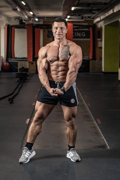 Man in Black Shorts Flexing Muscles