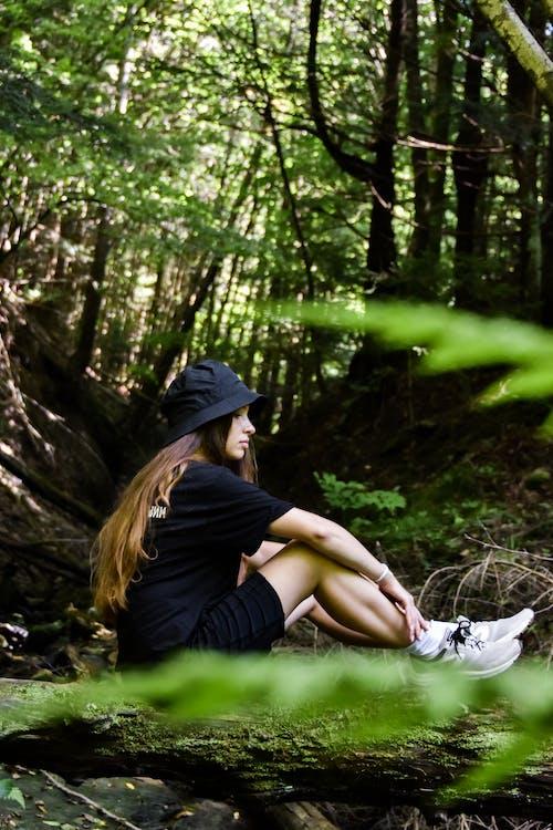 Woman in Black Shirt and Blue Denim Shorts Sitting on Brown Tree Log