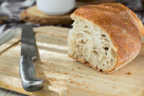 在褐色的木砧板上切面包和不锈钢刀