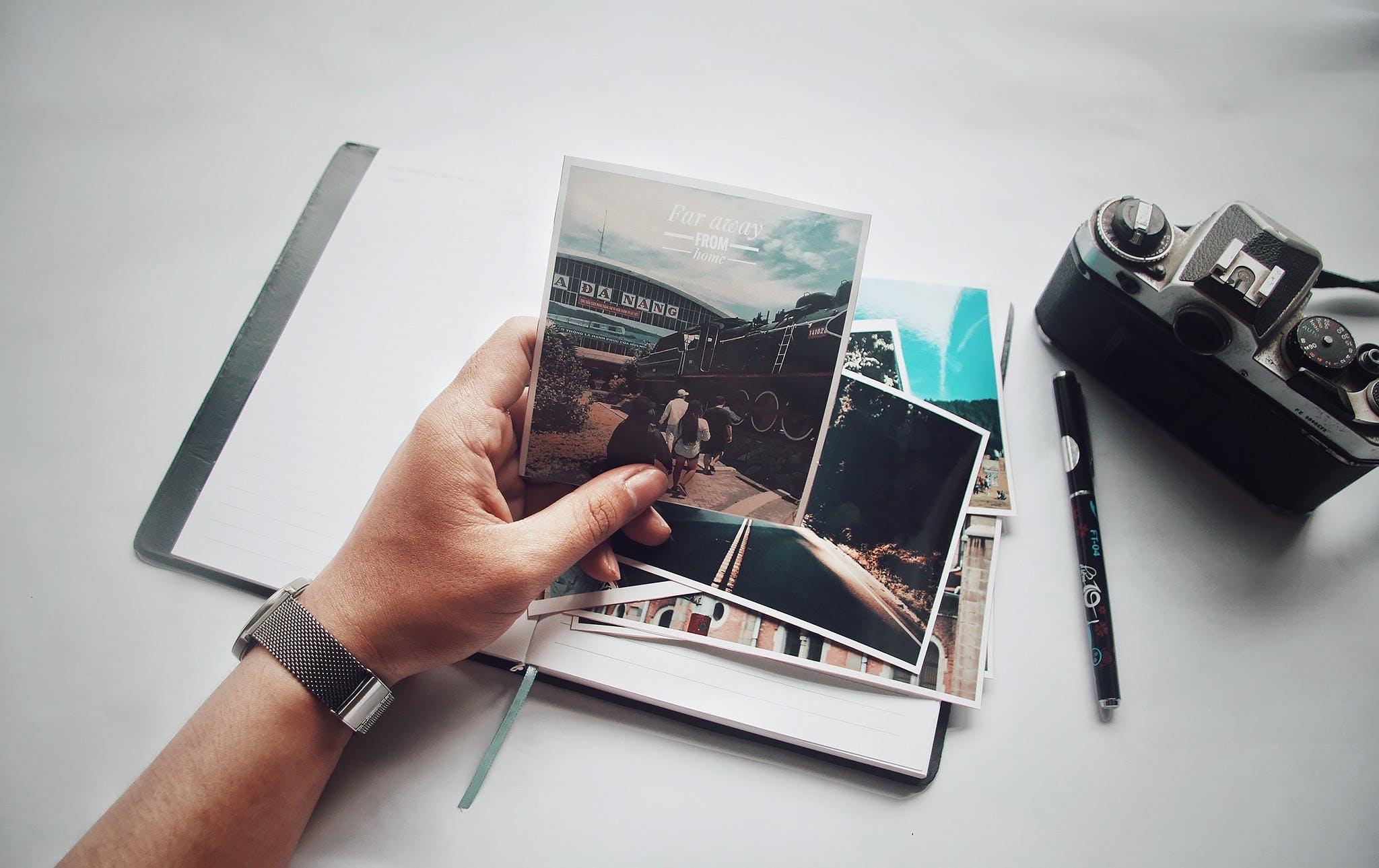Kostenloses Stock Foto zu hand, kamera, schreibtisch, stift