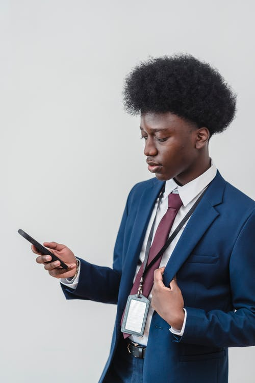 A Man in a Suit Using His Cellphone