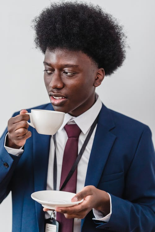 Man in Blue Suit Holding White Ceramic Mug