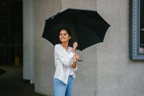 Photo of Woman Wearing White Long-sleeved Shirt and Blue Jeans Holding Black Umbrella