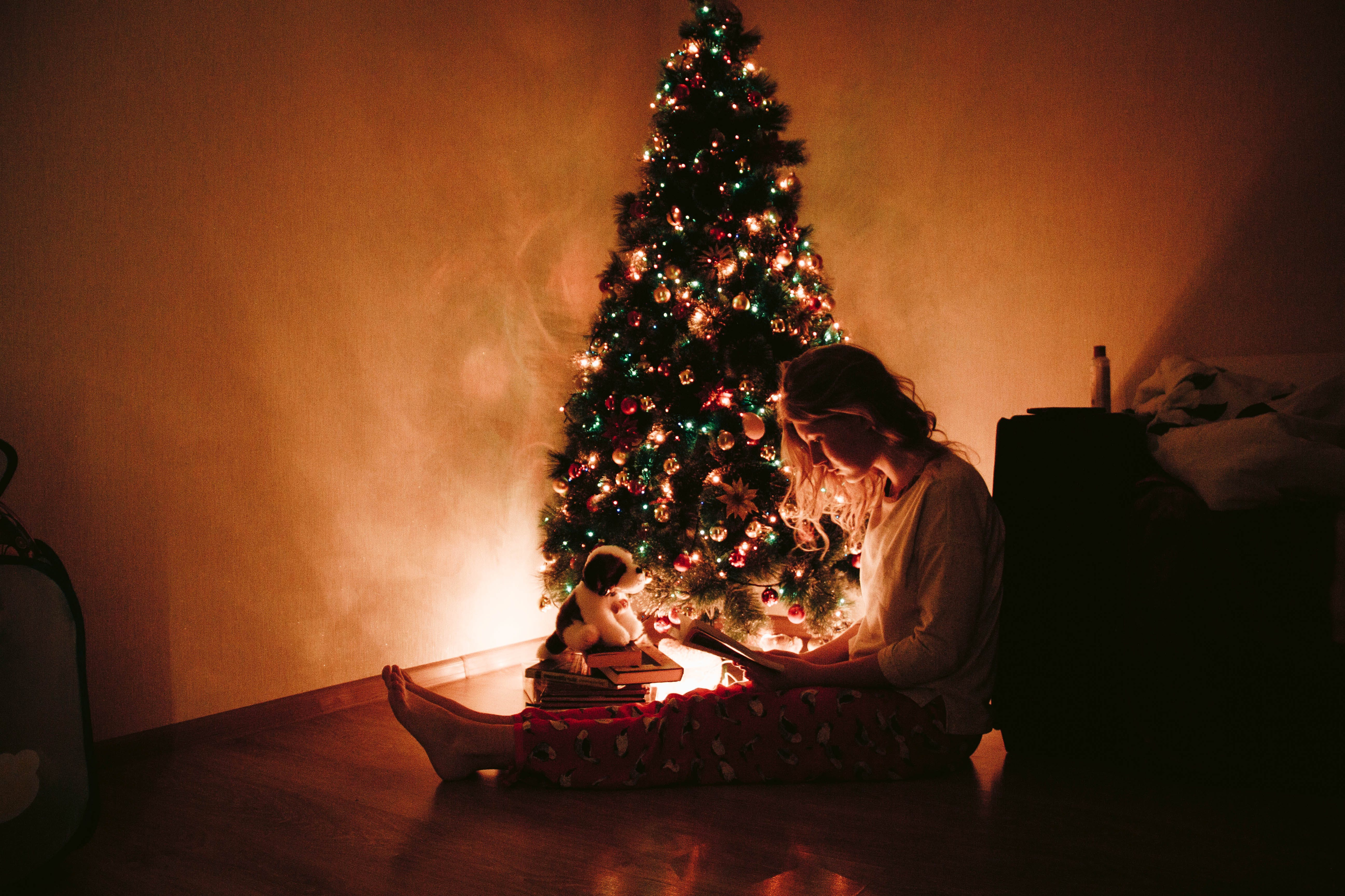 Photo of Woman Sitting Near the Christmas Tree