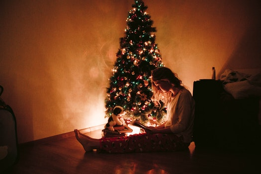 Photo of Woman Sitting Near the Christmas Tree