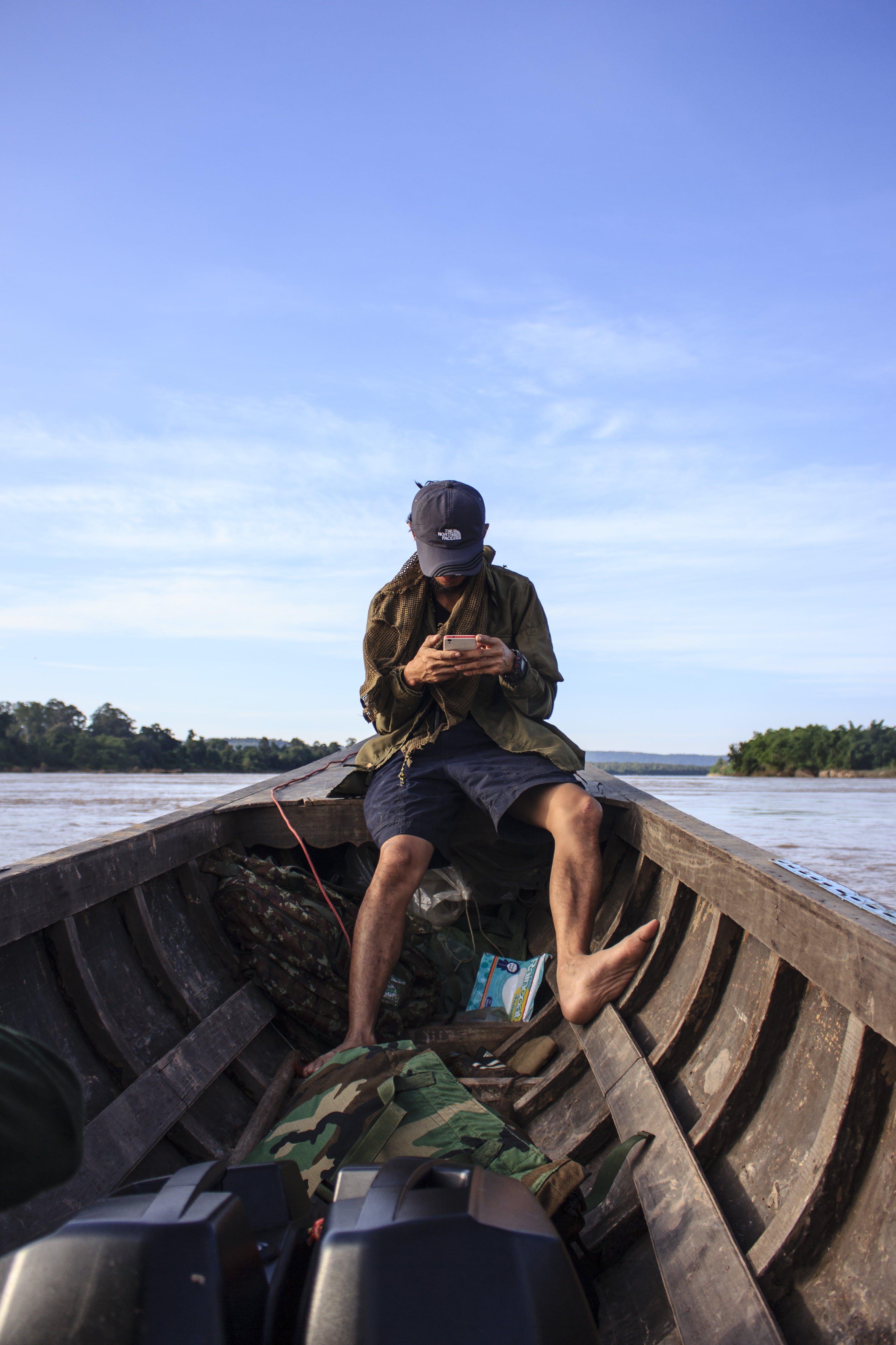 Man Wearing Black Cap Sitting Inside a Boat