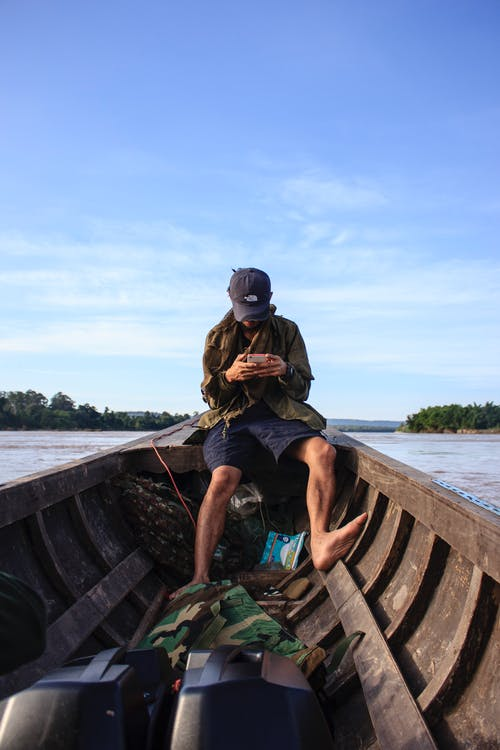 Kostenloses Stock Foto zu bäume, boot, fischer, handy