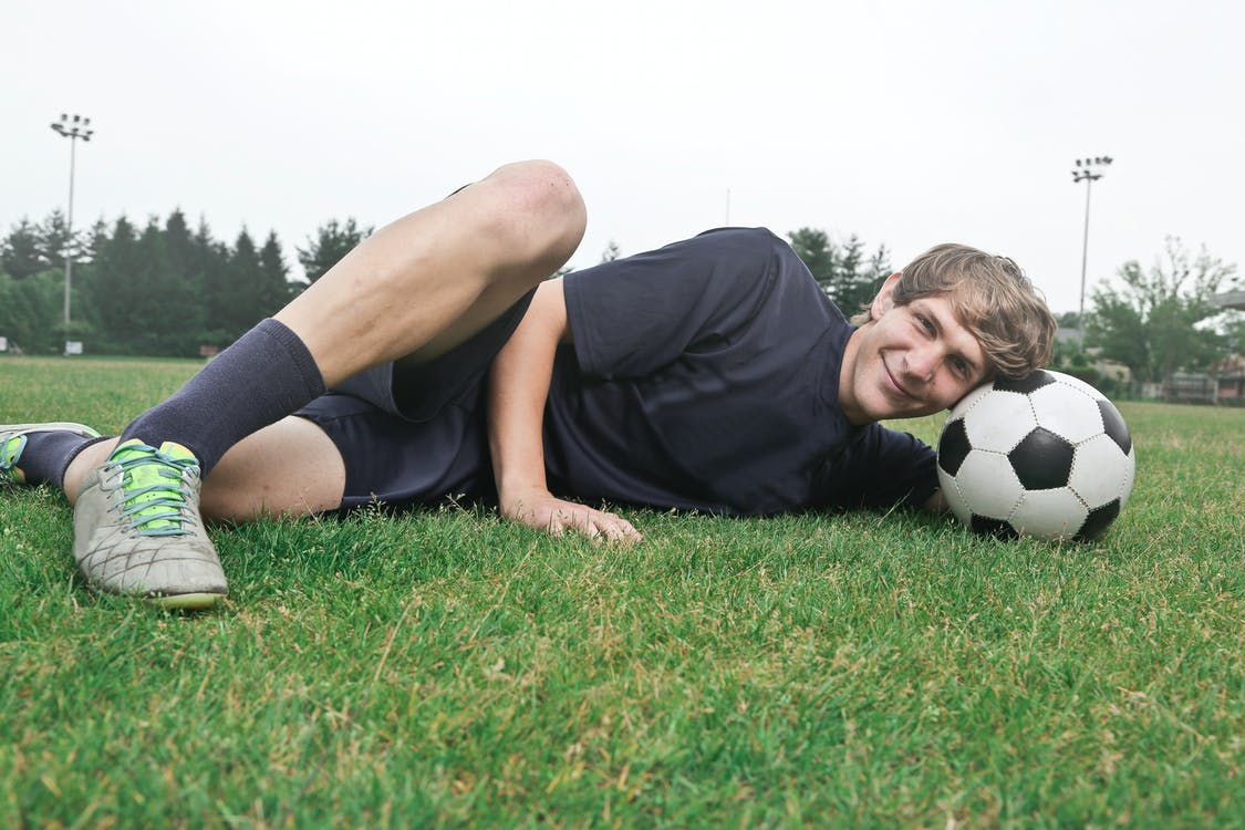 Man Wearing Black Crew-neck Shirt and Black Shorts Lying on Green Grass at Daytime