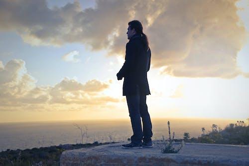 Man Wearing Black Coat Standing Near Sea during Golden Hour