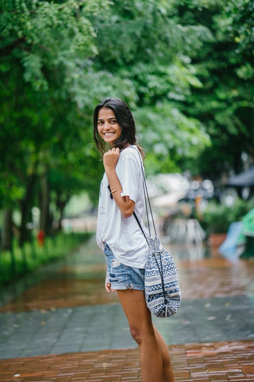 Shallow Focus Photography of Woman in White Shirt and Blue Denim Shorts on Street Near Green Trees