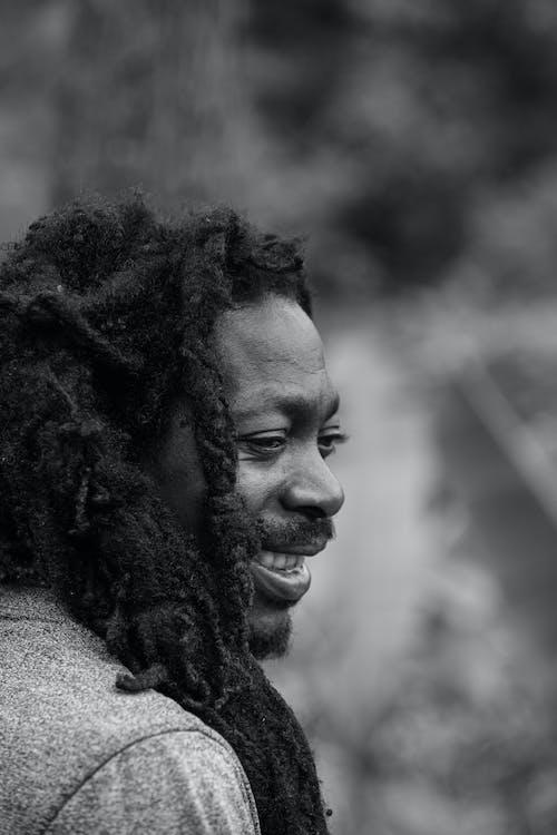 Monochrome Photo of a Man with Dreadlocks Smiling