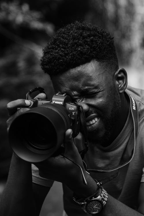 Grayscale Photo of a Man Holding a Dslr Camera