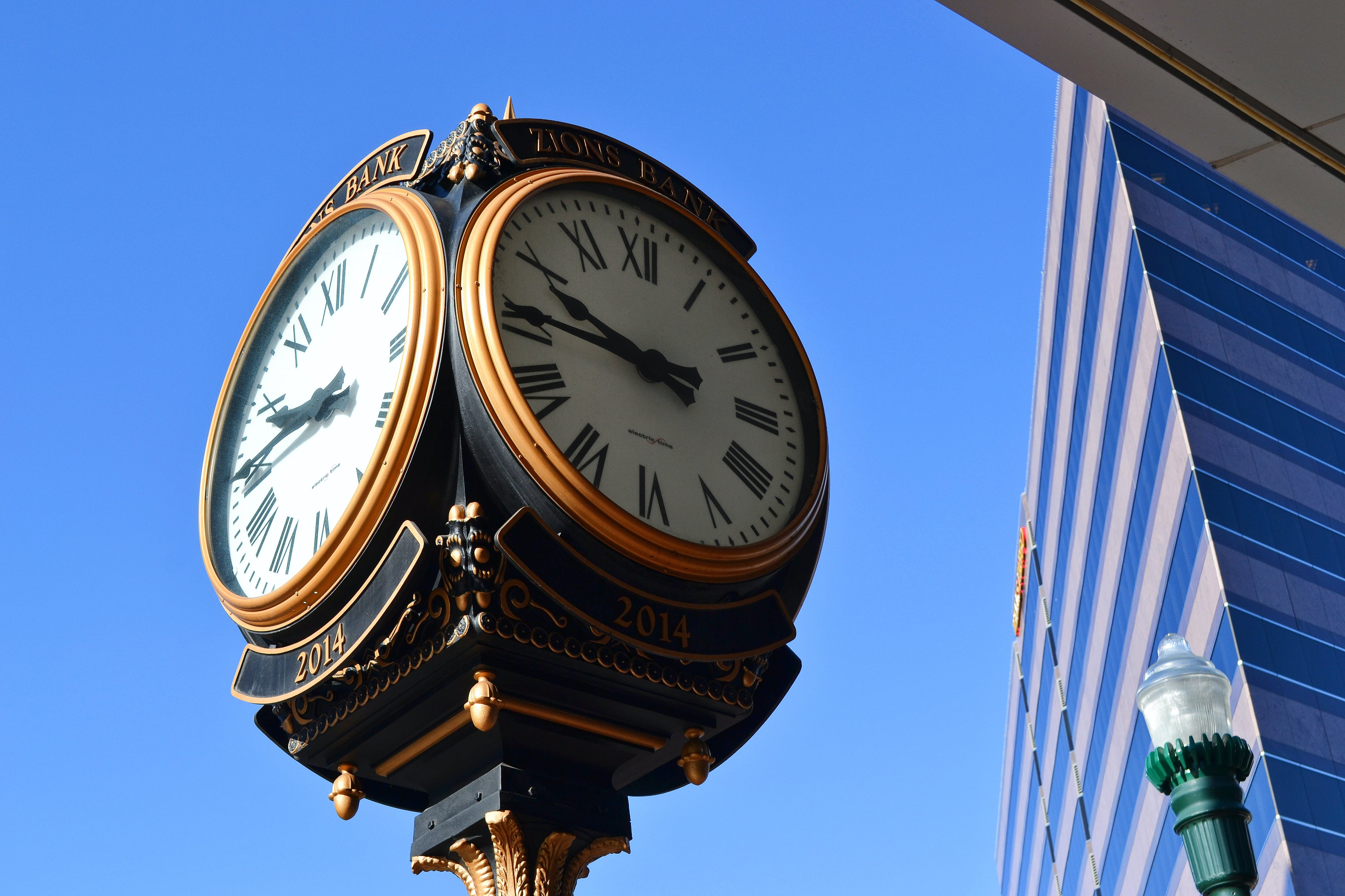 Close-up Photo of Street Clock Near Tall Building