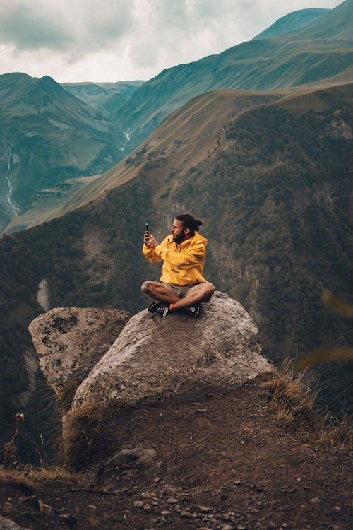 Man in Brown Jacket Sitting on Rock