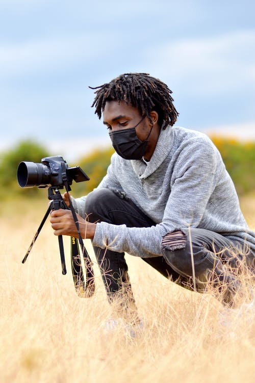 Man in Face Mask Wearing Gray Sweater Holding Black Camera While Sitting in the Field